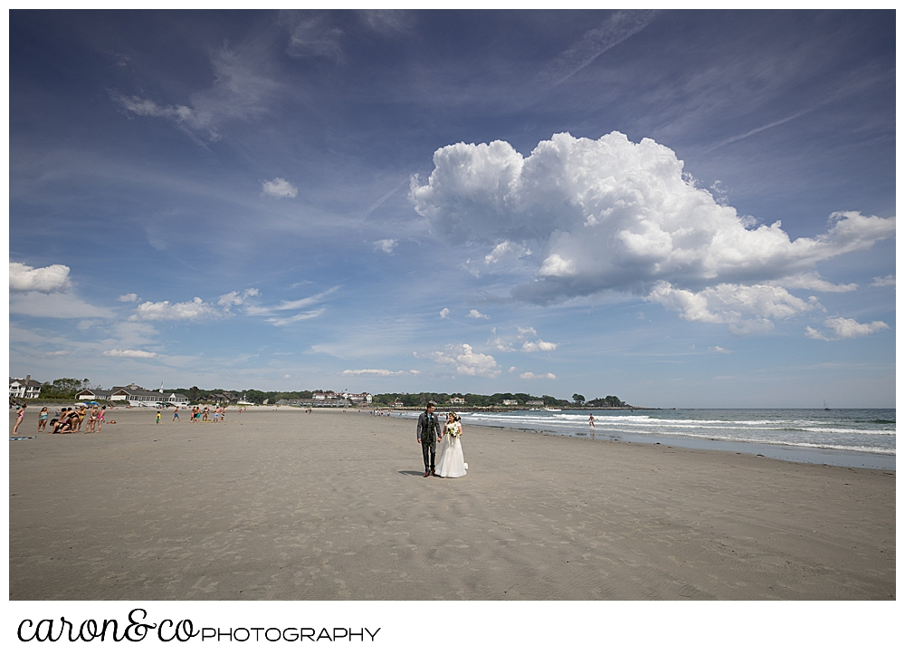 a bride and groom walk along Gooch's Beach in Kennebunk, Maiane