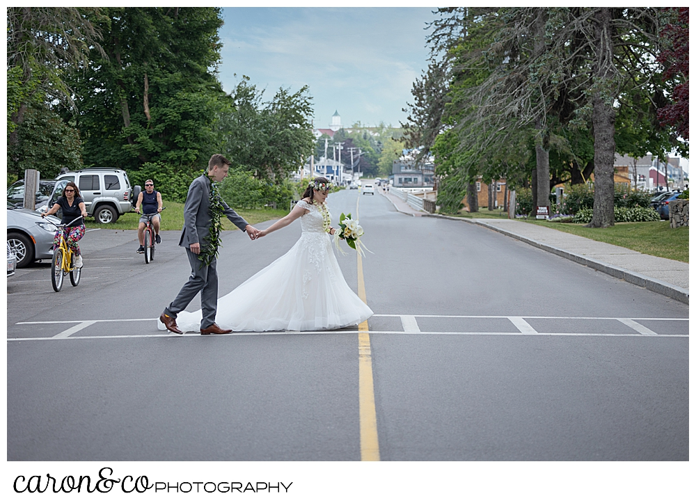 a bride and groom holding hands, cross the street on Ocean Avenue, Kennebunkport, Maine