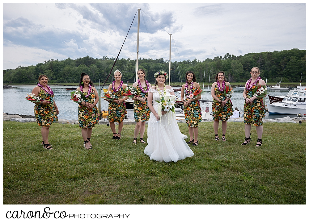 a bride wearing white, is surrounded by 7 bridesmaids wearing short, hawaiian dresses, on the river's edge at a Nonantum Resort tented wedding