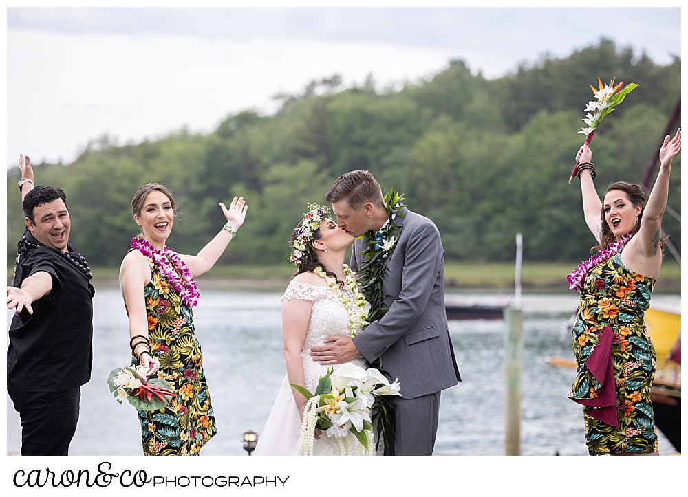 a bride and groom kiss, white their bridal party cheers next to them, at their Nonantum Resort tented wedding