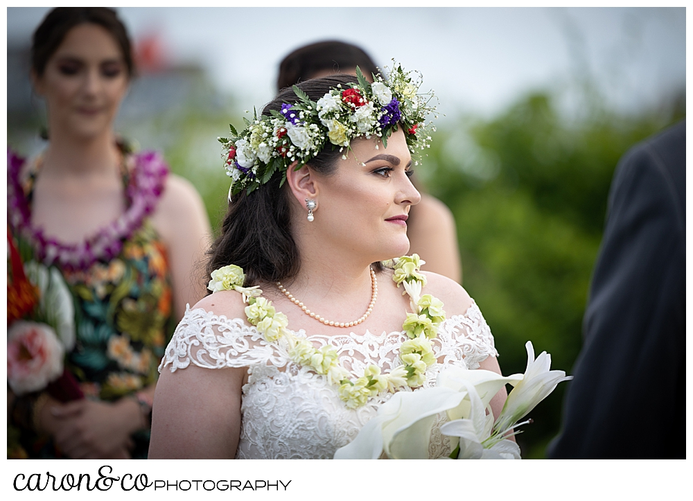 a bride wearing a white dress, a flowered headpiece, and a white lei, looks towards her groom during their outdoor wedding ceremony at the Nonantum Resort Kennebunkport, Maine
