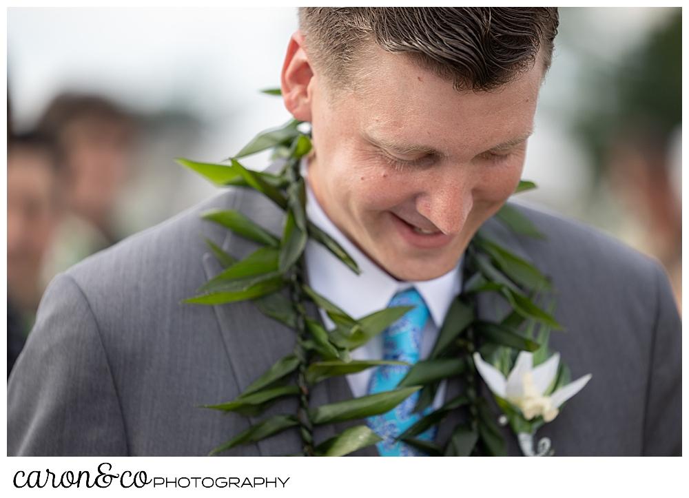 a groom smiles during a hawaiian themed wedding ceremony