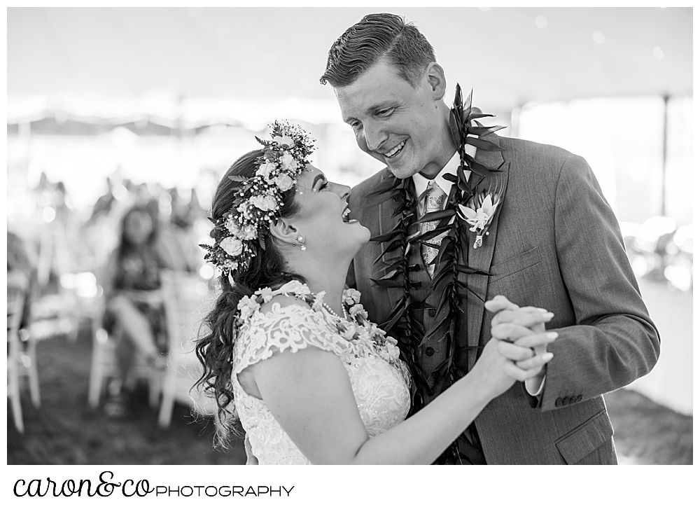 black and white photo of a bride and groom laughing together as they enjoy their first dance at their Nonantum Resort tented wedding