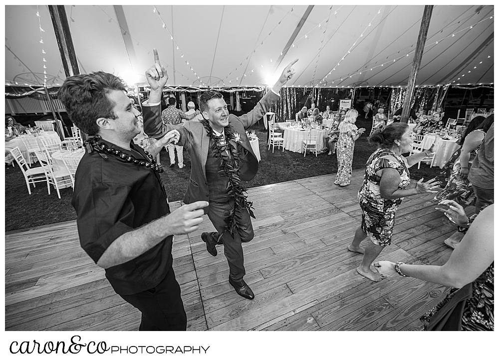 black and white photo of guests dancing , two men are in the foreground, at a Nonantum Resort tented wedding