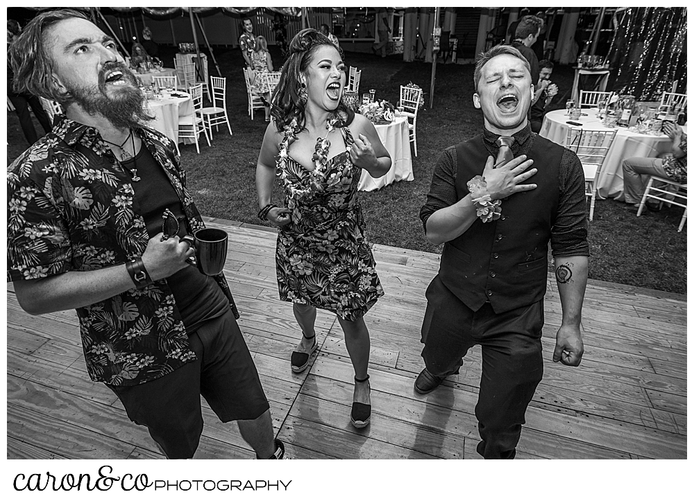 black and white photo of guests singing to the music at a Nonantum Resort tented wedding reception
