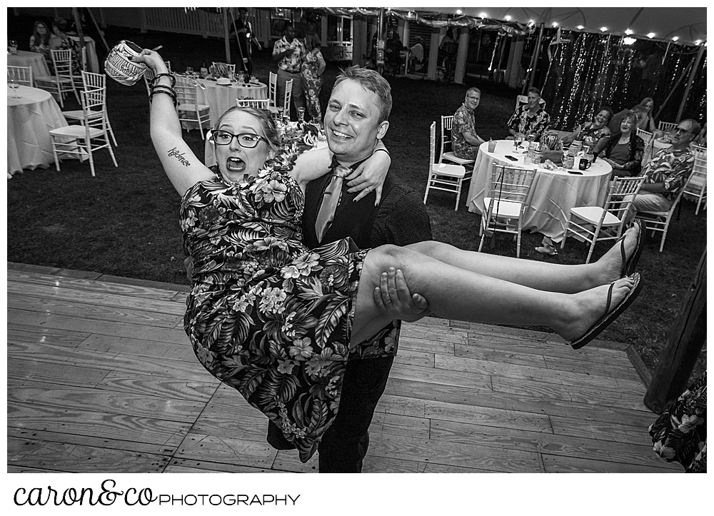black and white photo of a man holding a woman and spinning her around, during a wedding reception