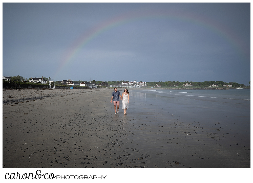 a man and woman walk on Gooch's Beach in Kennebunk, Maine, with a rainbow overhead