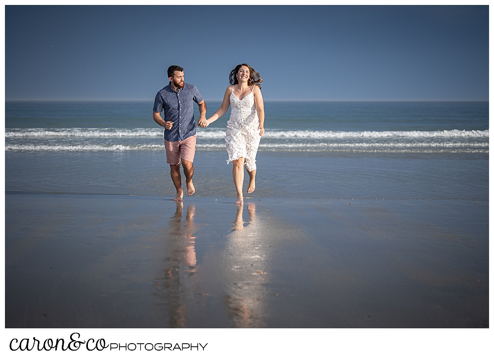 a man and woman run in the surf at Gooch's Beach, during their Kennebunkport engagement session