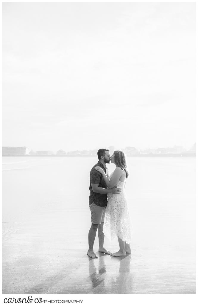 a black and white photo of a man and woman kissing on Gooch's Beach, Kennebunk, Maine