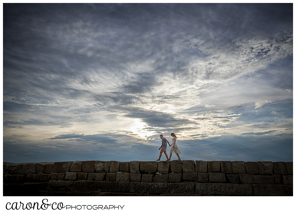 a man and woman walk on the breakwater in Kennebunkport, Maine, during their Kennebunkport engagement session