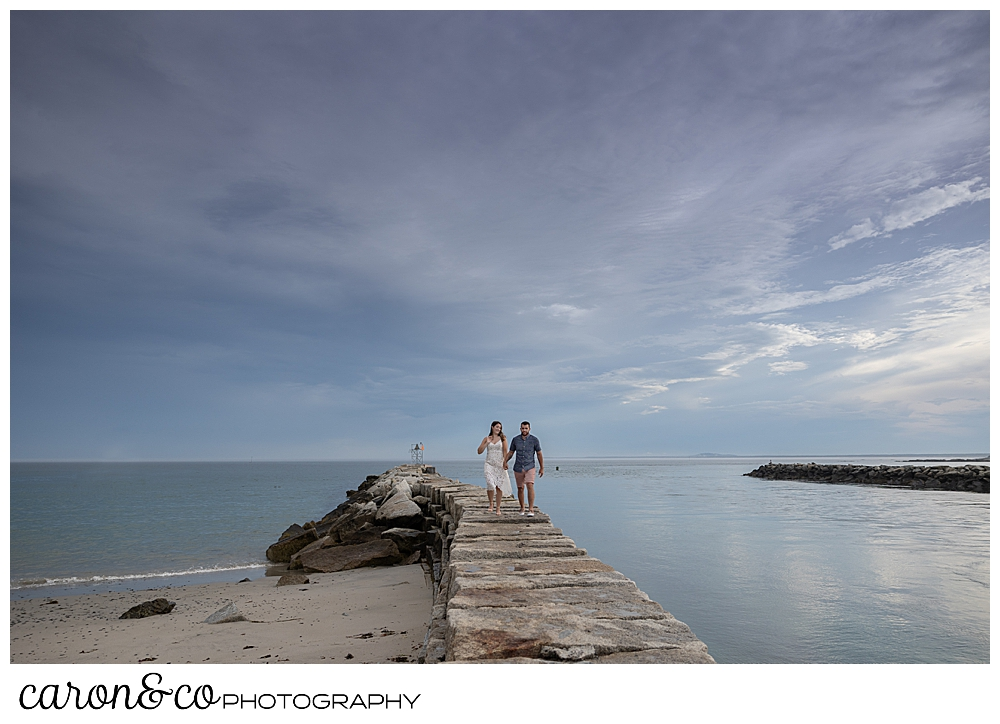 a man and woman walk on the Kennebunkport Maine breakwater, during their Kennebunkport engagement session