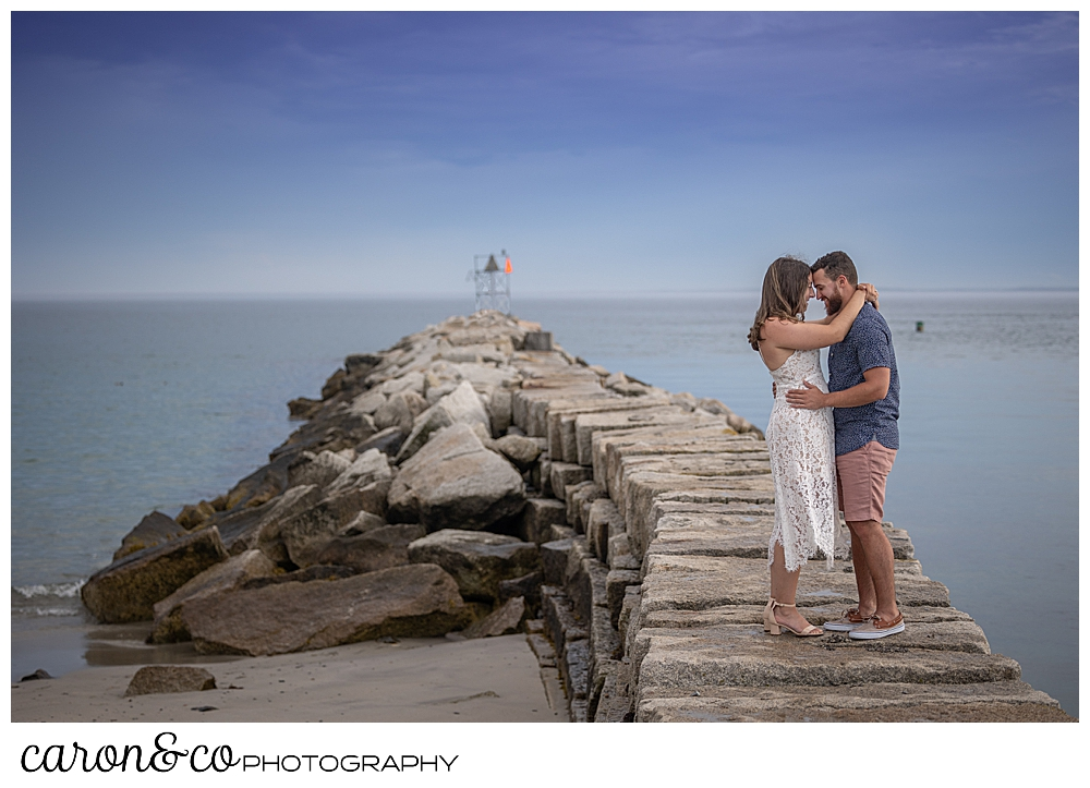 a man and woman stand together with their foreheads together on the Kennebunkport Maine breakwater, during their Kennebunkport engagement session