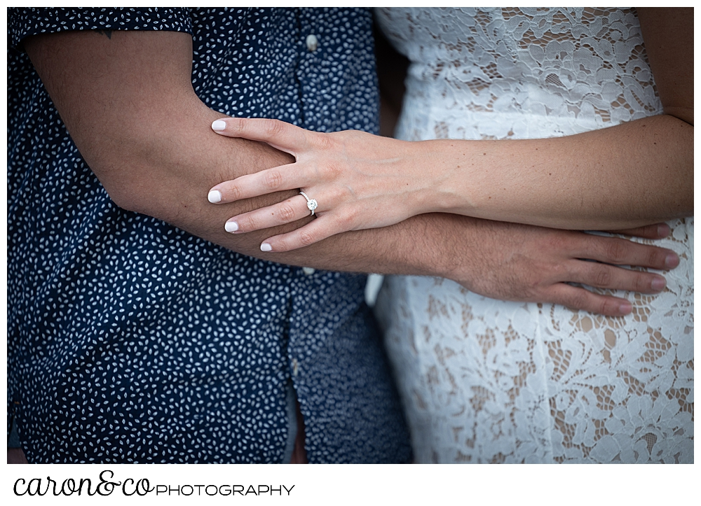 the torso of a man and woman hugging each other, the woman has an engagement ring, during their Kennebunkport engagement session