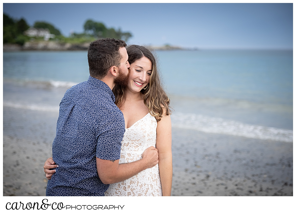 a man kisses a woman on the forehead at Colony Beach, during their Kennebunkport engagement session