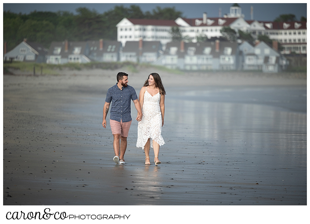 a man and woman hold hands and walk near the water at Gooch's Beach in Kennebunk, Maine, during their Kennebunkport engagement session, the Colony Hotel in the background in Kennebunkport, Maine