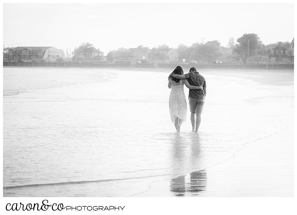 black and white photo of a man and woman, their arms around each other, on Gooch's beach, Kennebunk, Maine, walking away from the camera during their Kennebunkport engagement session