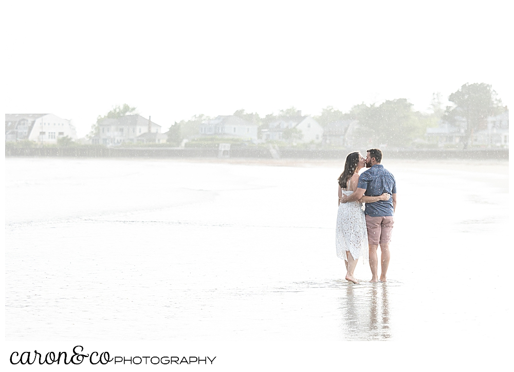 a man and woman, their backs to the camera, kiss each other at Gooch's Beach, Kennebunk, Maine, during their Kennebunkport engagement session