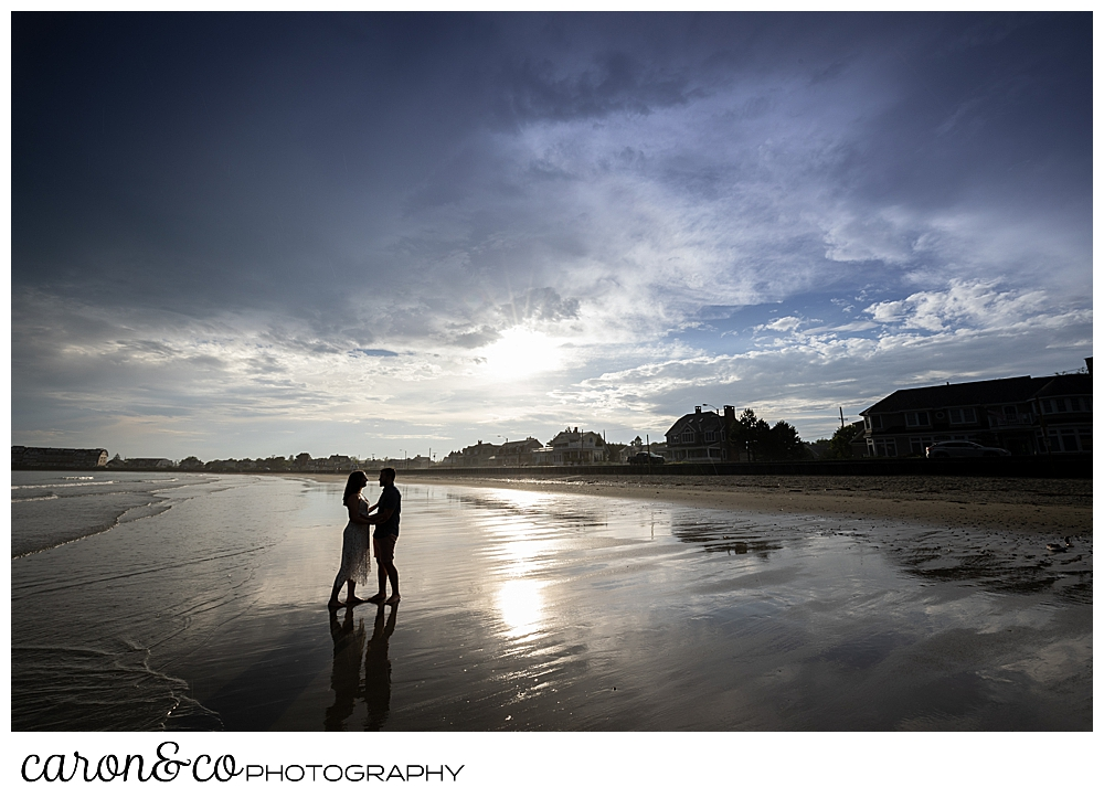 a man and woman stand together at Gooch's Beach in Kennebunk, Maine, during a Kennebunkport engagement session