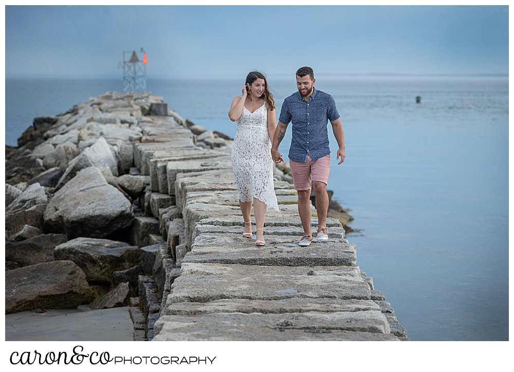 a man and woman walk hand in hand on the Kennebunkport Maine breakwater, during their Kennebunkport engagement session