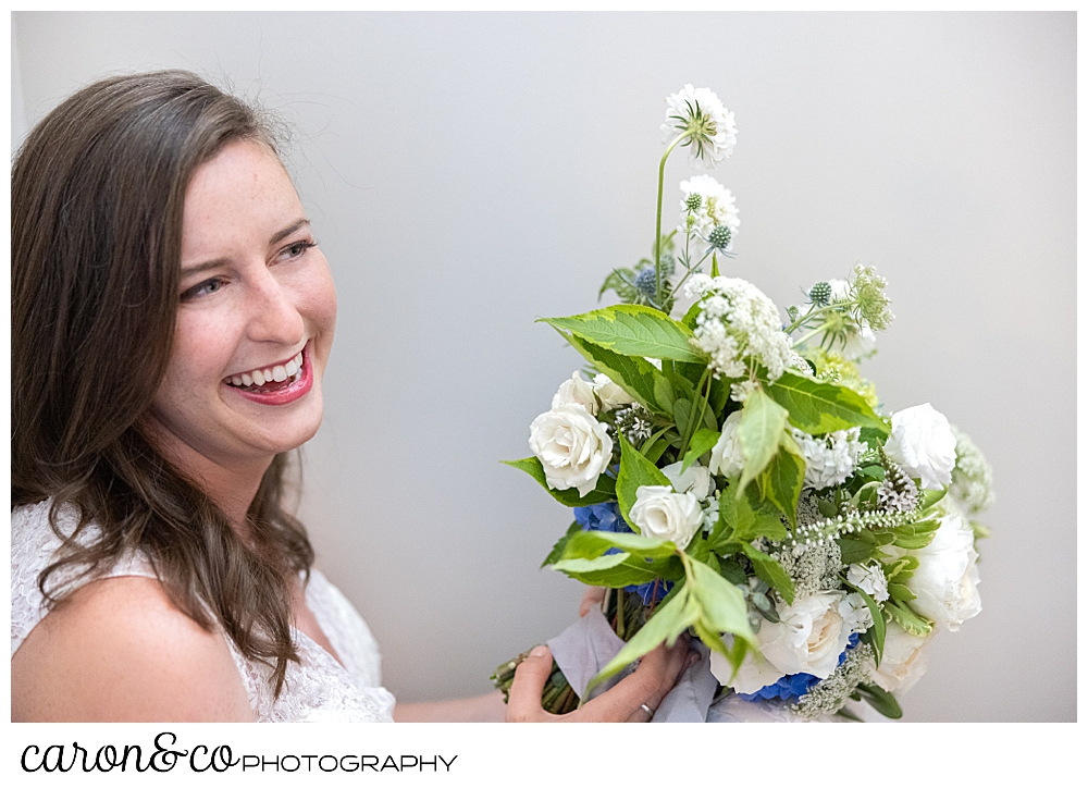 a smiling bride holding a bouquet of white flowers with greens