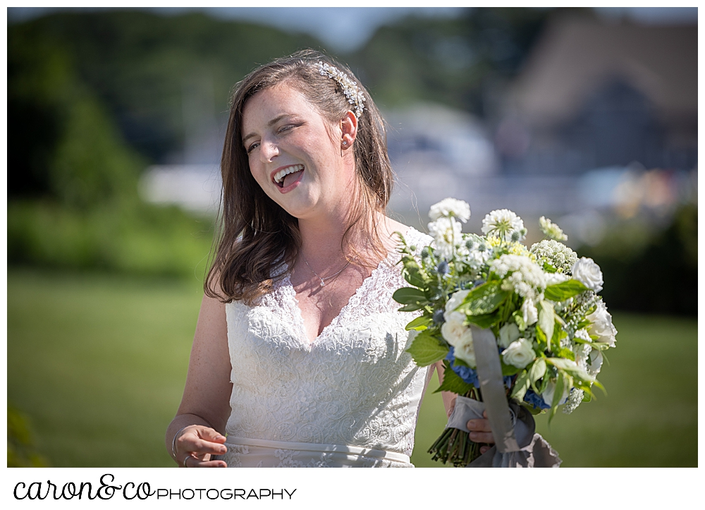 a bride, standing outside on a green lawn, is smiling, and holding a white and green bouquet