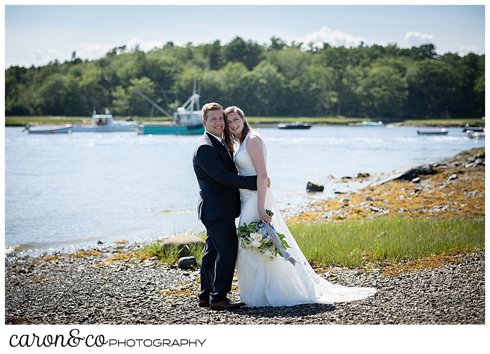 bride and groom hugging each other, on the banks of the Kennebunk River. They're looking at the camera