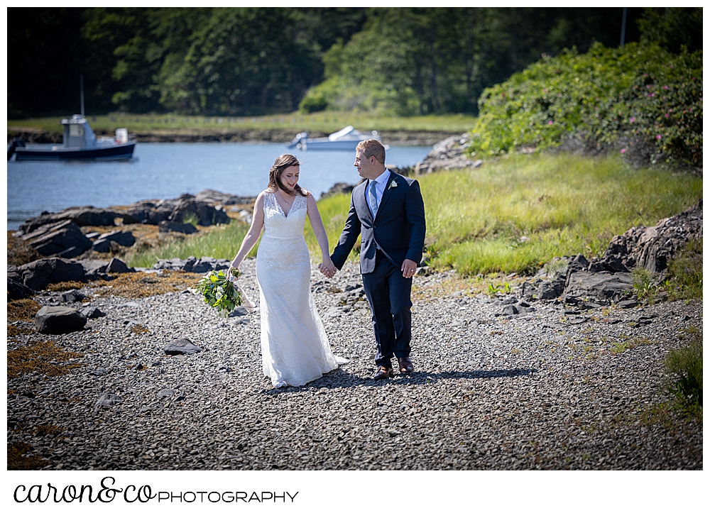 a bride and groom, holding hands as they walk on a beach on the Kennebunk River.