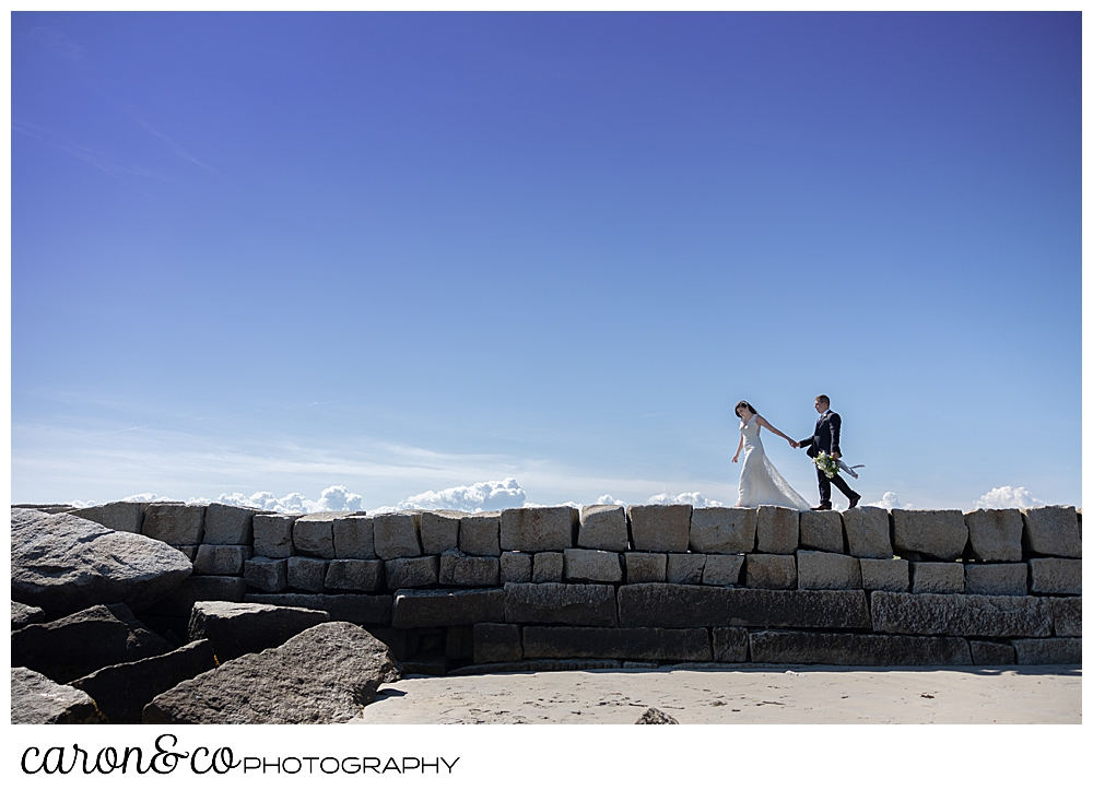 a bride and groom walk along the top of the Kennebunkport Breakwater, holding hands