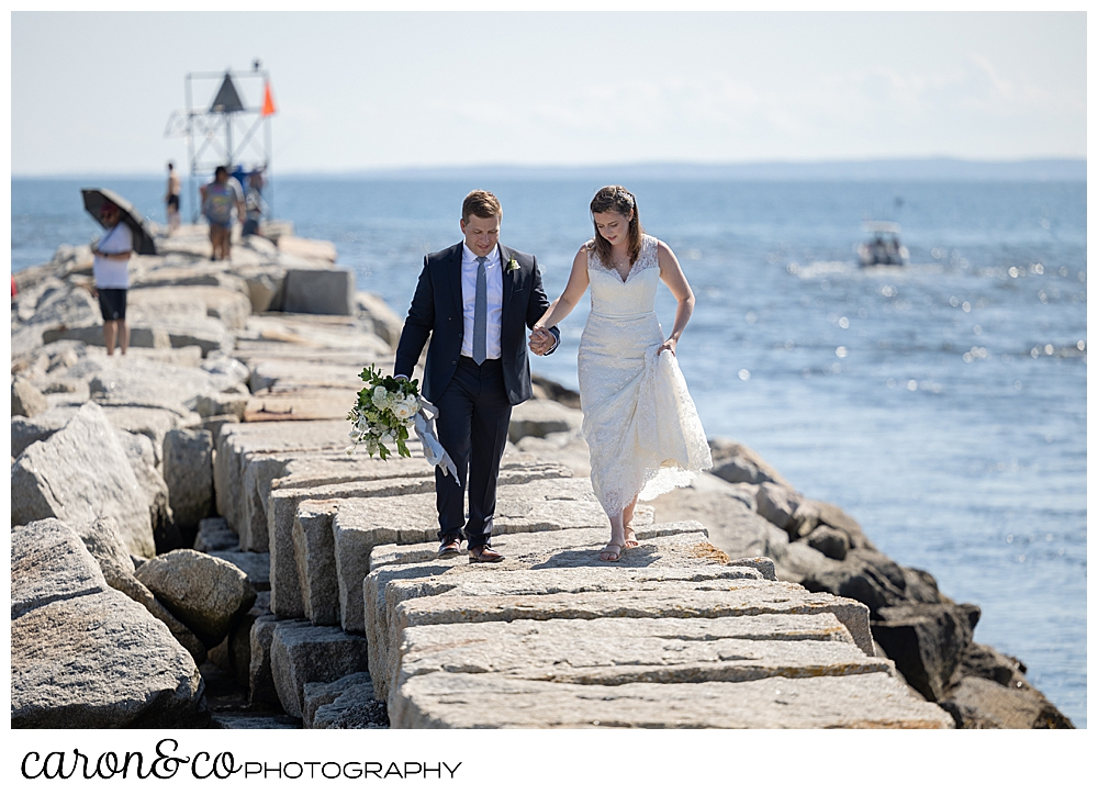 a bride and groom walk on the top of the Kennebunkport Breakwater, they're holding hands