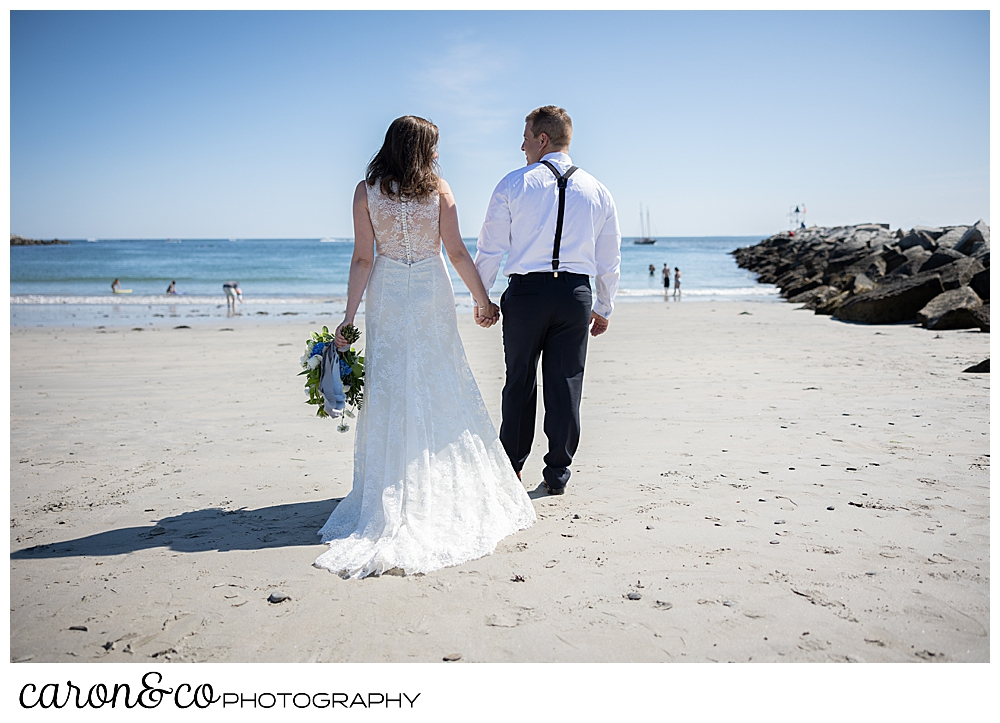 a bride and groom, holding hands, walk away from the camera towards the water at Colony Beach, Kennebunkport, Maine
