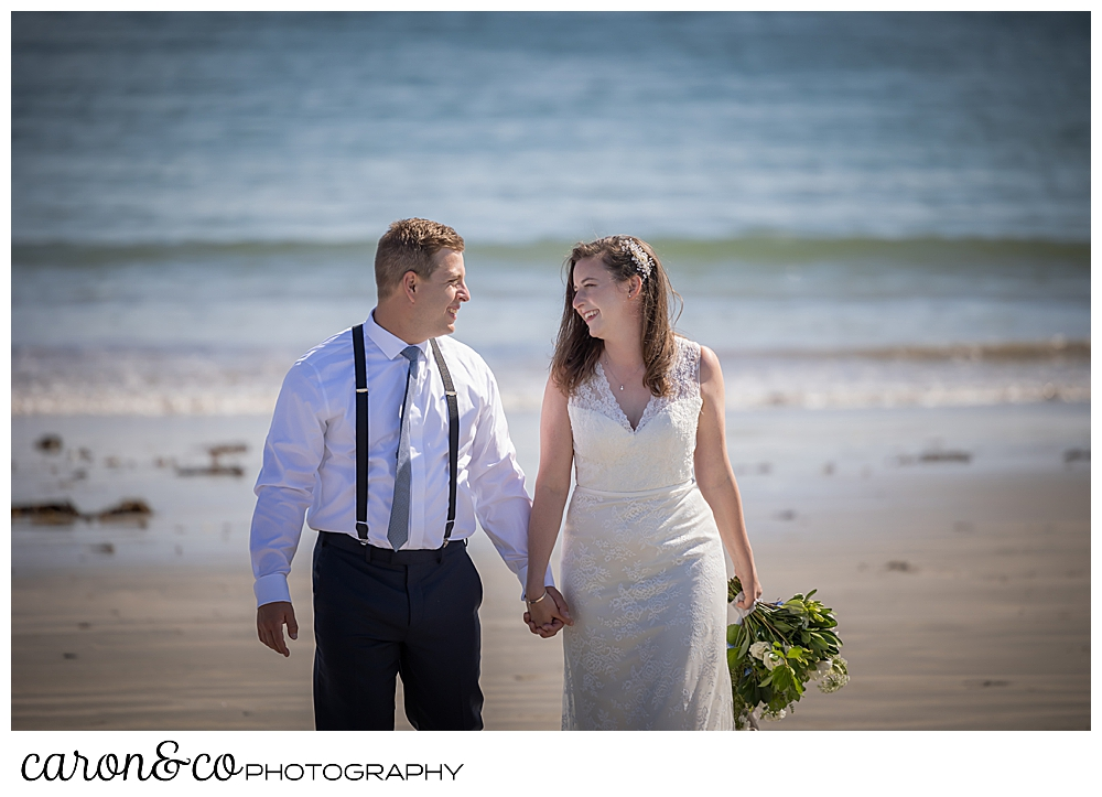 a bride and groom holding hands and walking on the beach, walking towards the camera