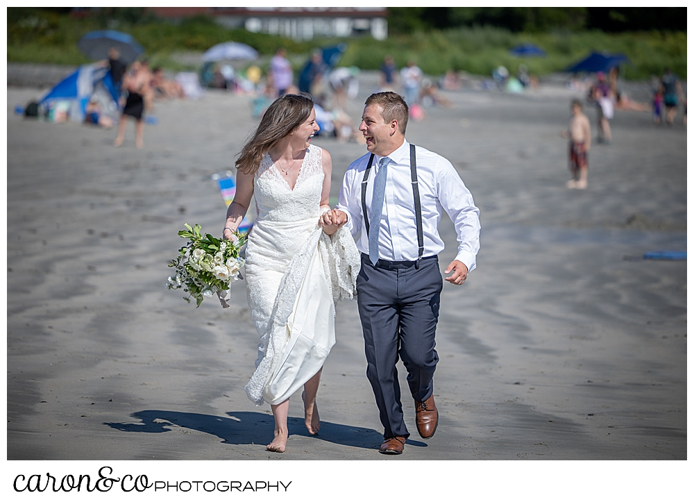a bride and groom are holding hands, laughing at each other, and running on the beach towards the camera
