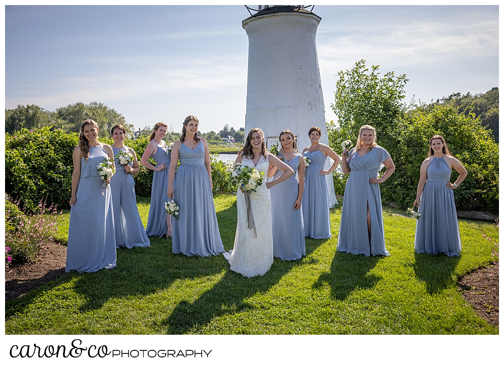 a bride and her bridesmaids stand in a line in front of the lighthouse at the Nonantum Resort, Kennebunkport, Maine