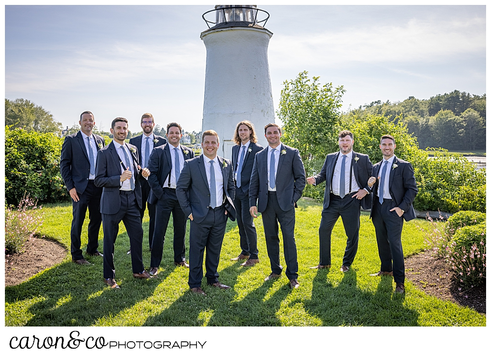a groom and his groomsmen stand together in front of the lighthouse at the Nonantum Resort, Kennebunkport, Maine