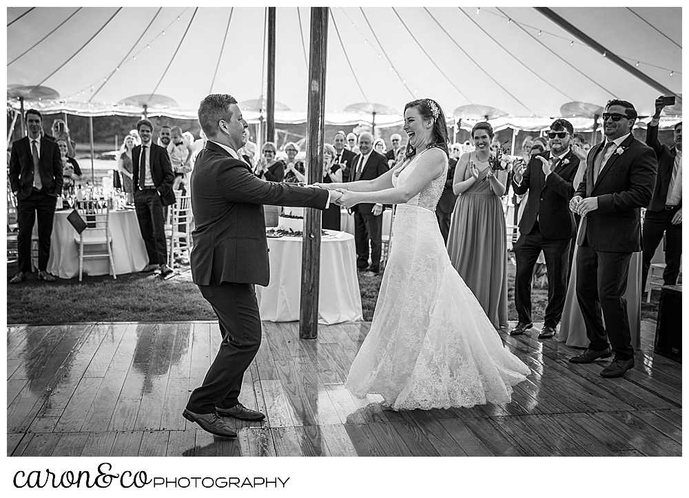 black and white photo of a bride and groom dancing their first dance under the Sperry Tents Seacoast tent, and their Nonantum Resort wedding celebration