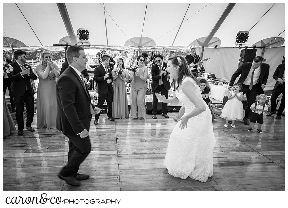 black and white photo of a bride and groom dancing at their Nonantum Resort wedding celebration, their wedding party is surrounding the dance floor