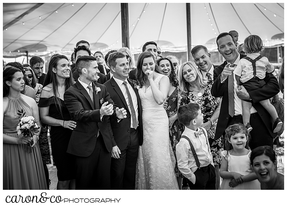 black and white photo of a bride and groom and their guests paying tribute to the past year of their highs and lows, during their Nonantum Resort wedding celebration