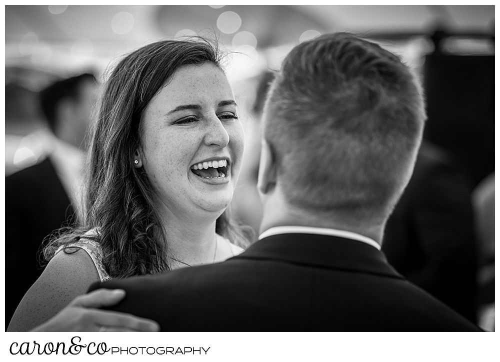 black and white photo of a bride smiling at her groom as they dance their first dance at their Nonantum Resort wedding celebration