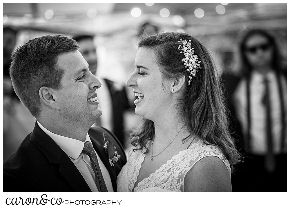 black and white photo of a bride and groom smiling at one another as they dance their first dance at their Nonantum Resort wedding celebration