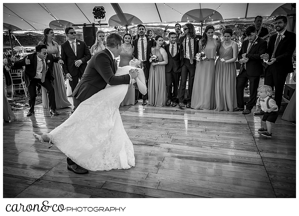 black and white photo of a bride and groom dancing, the groom is dipping the bride, as their bridal party looks on from the edge of the dance floor at a Nonantum Resort wedding celebration