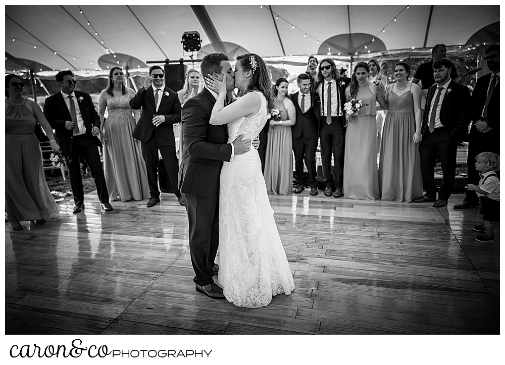 black and white photo of a bride and groom kissing during their dance while their bridal party watches from the side of the dance floor, at a Nonantum Resort wedding celebration