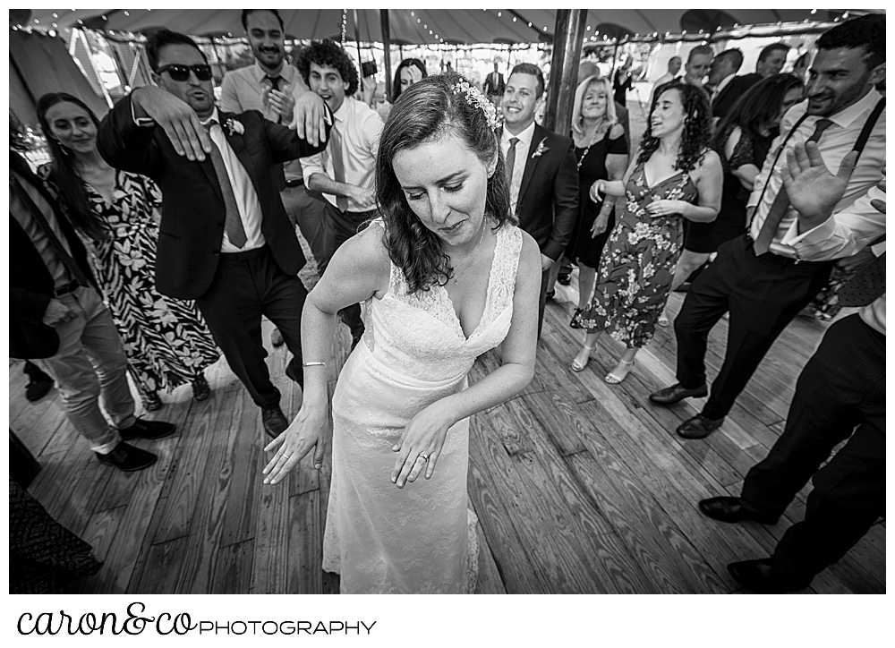 black and white photo of a bride dancing at her Nonantum Resort wedding celebration, she's surrounded by wedding guests