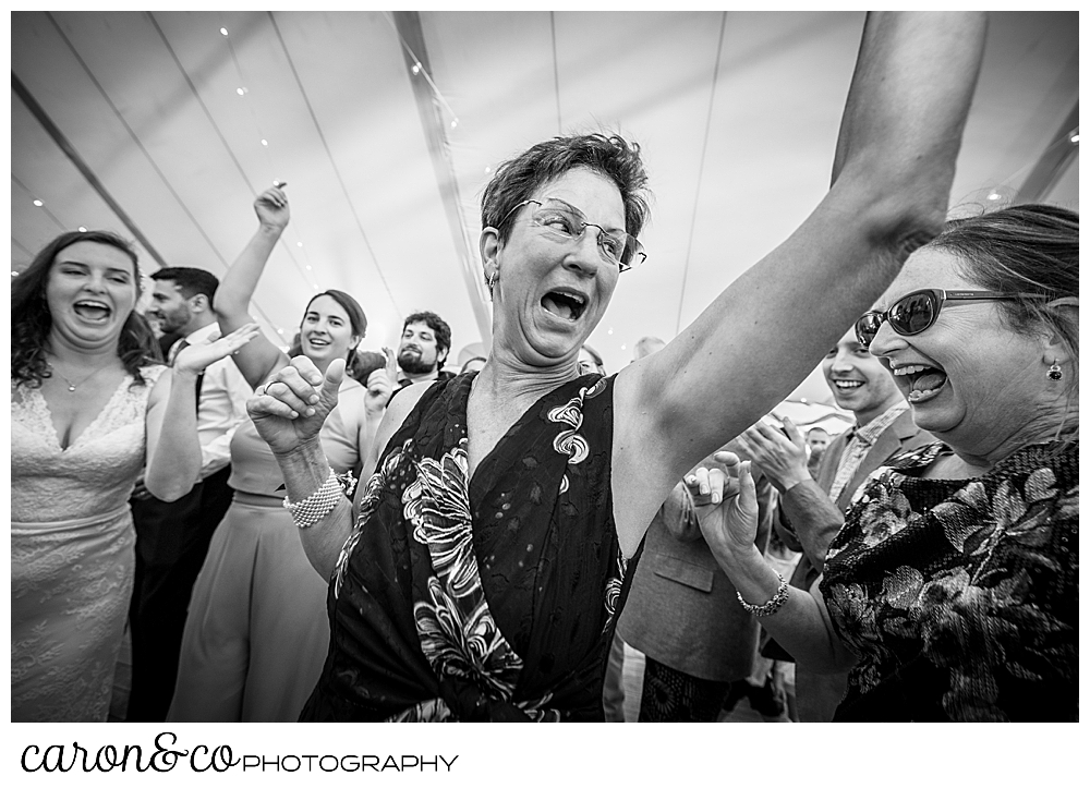 black and white photo of a woman dancing in the foreground, there are people dancing around her