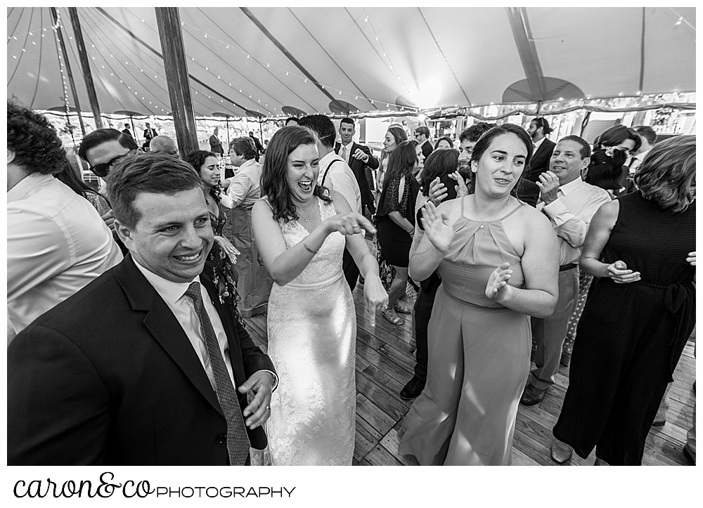 black and white photo of a bride dancing with her friends