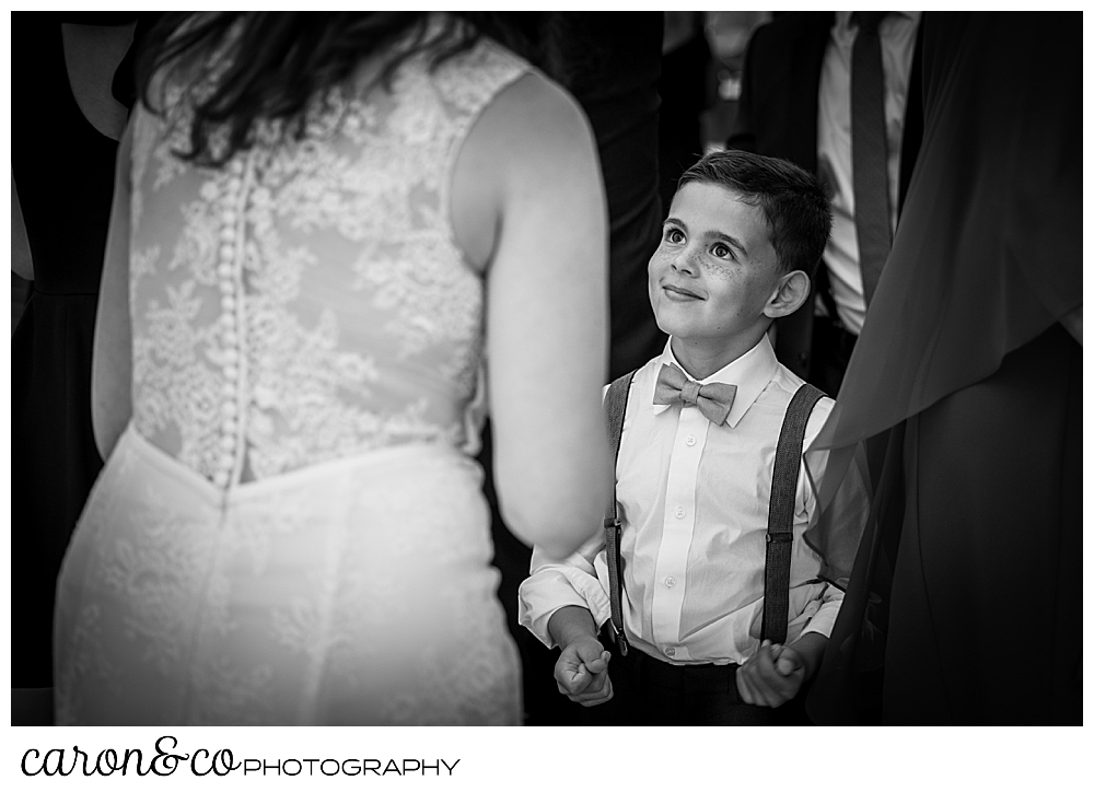 black and white photo of a boy looking up at a bride, the bride's back is to the camera