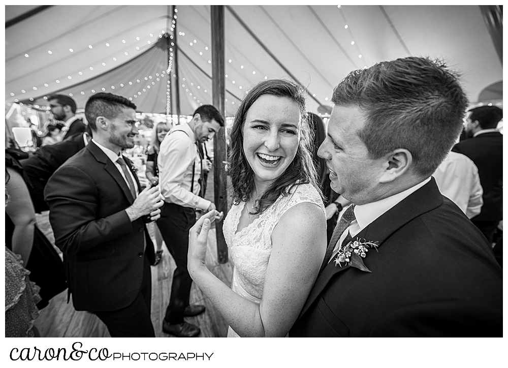 black and white photo of a bride turning to smile at her groom, while they're dancing during a Nonantum Resort wedding celebration