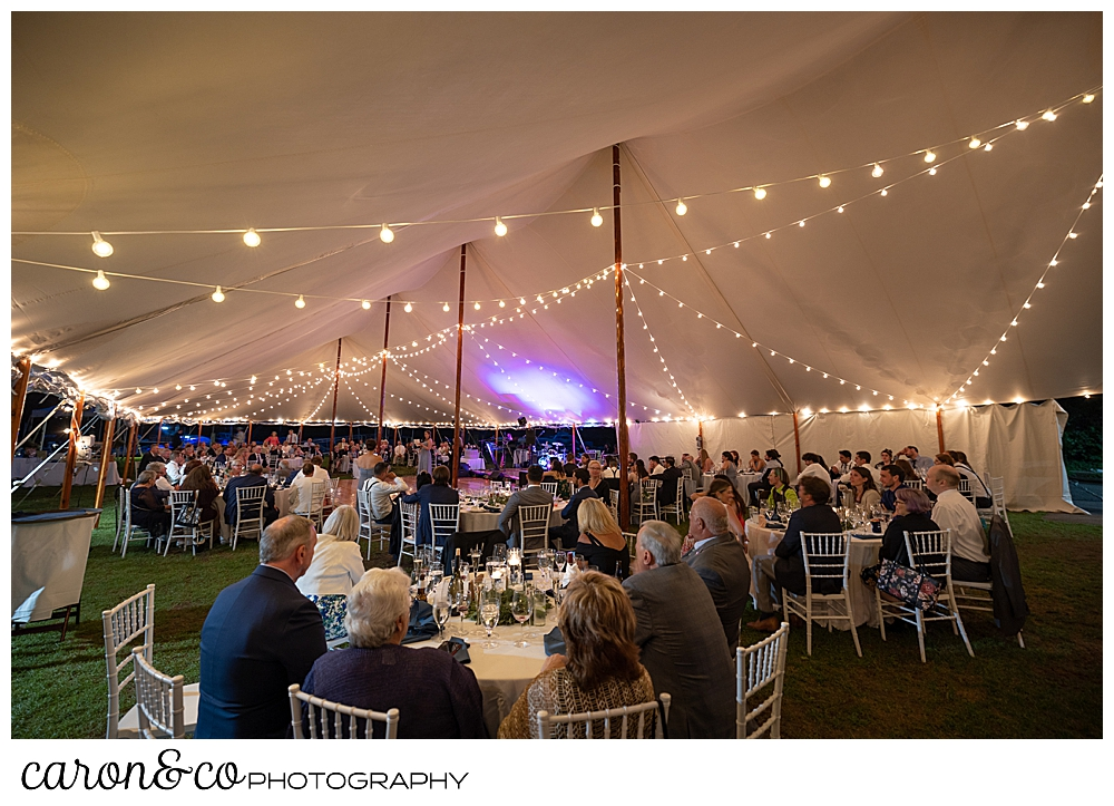 guests are seated at round tables under a Sperry Tent Seacoast tent, at a Nonantum Resort wedding celebration