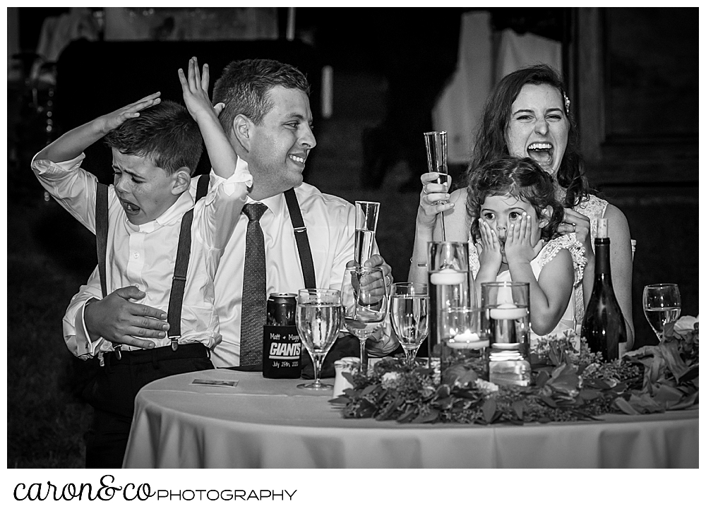 black and white photo of a bride and groom sitting at their sweetheart table, holding a niece and nephew, during toasts at their Nonantum Resort wedding celebration