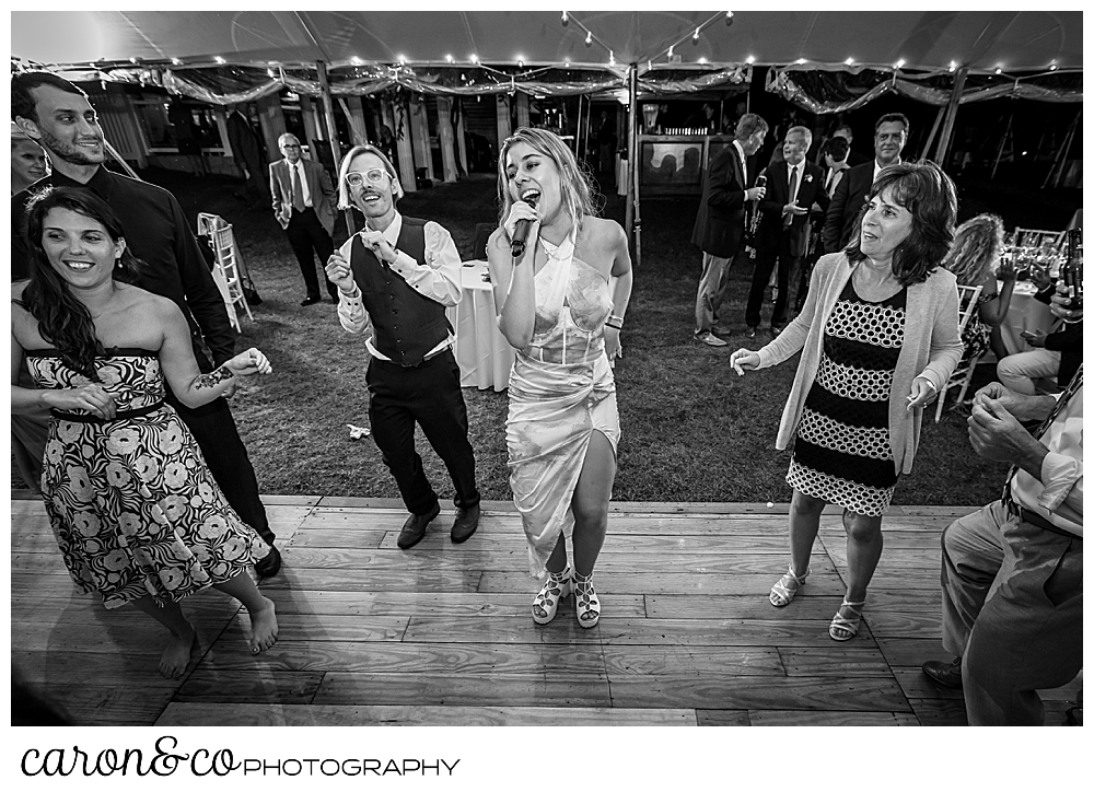 black and white photo of a member of the band Cover Story Entertainment, singing on the dance floor among wedding guests at a Nonantum Resort wedding celebration