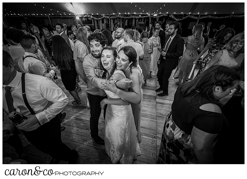 black and white photo of a bride and her friends hugging in the middle of the dance floor during a Nonantum Resort wedding celebration
